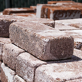 Masonry products including bricks and pavers stacked in yard