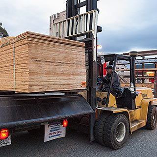 Forklift driver loads plywood for delivery