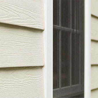 Window detail showing HardiePlank lap siding with wood grain texture complimented by HardieTrim trim boards