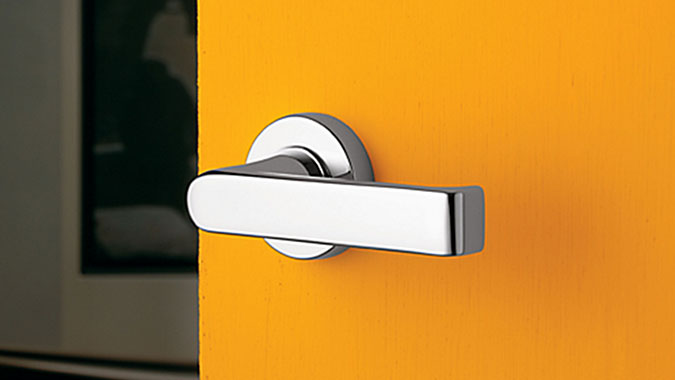 Very contemporary interior door lever in polished chrome on a yellow door is part of the Baldwin Estate Portfolio