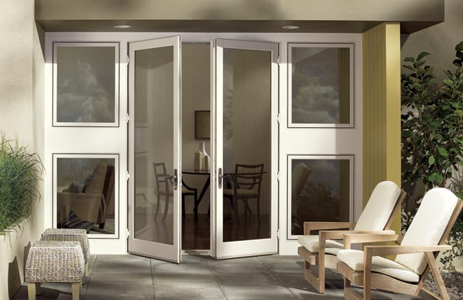 Integrity outswing French doors with satin nickel hardware transforms this small patio into an outdoor living space