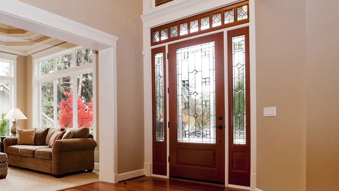 The interior of this foyer features the Mastermark Collection Venetia wood door with decorative glazing, sidelights and transom from Simpson Door Company