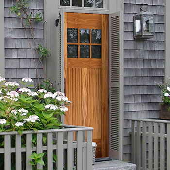 The coastal influence of this townhouse is found in the grey wood shingles and the natural wood door, part of the Nantucket Collection from Simpson Door Company