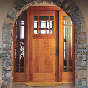 This stone entry features a custom made Craftsman style wood door with clear glass sidelites from T. M. Cobb