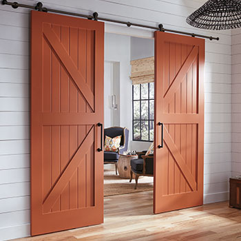 The focal point of this cottage interior is the pair of dark red MDF barn doors by Trustile