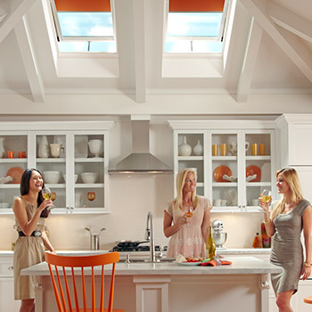 Two Velux skylights placed high in the ceiling fill the kitchen with daylight and provide lighting over the cooktop and island counter