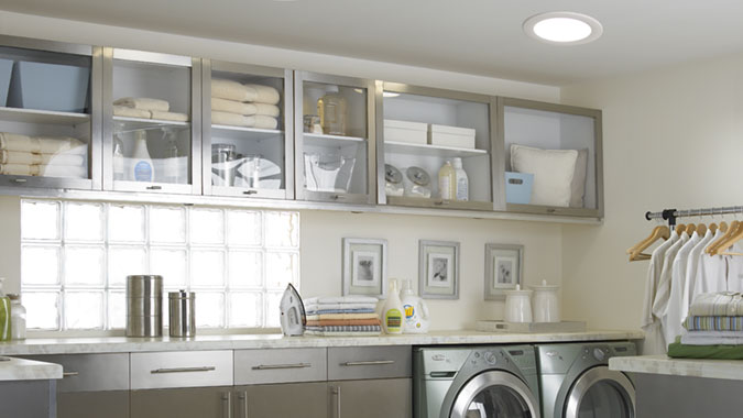 This light and airy laundry room is flooded with light from a pair of highly efficient Velux Sun Tunnel Skylights