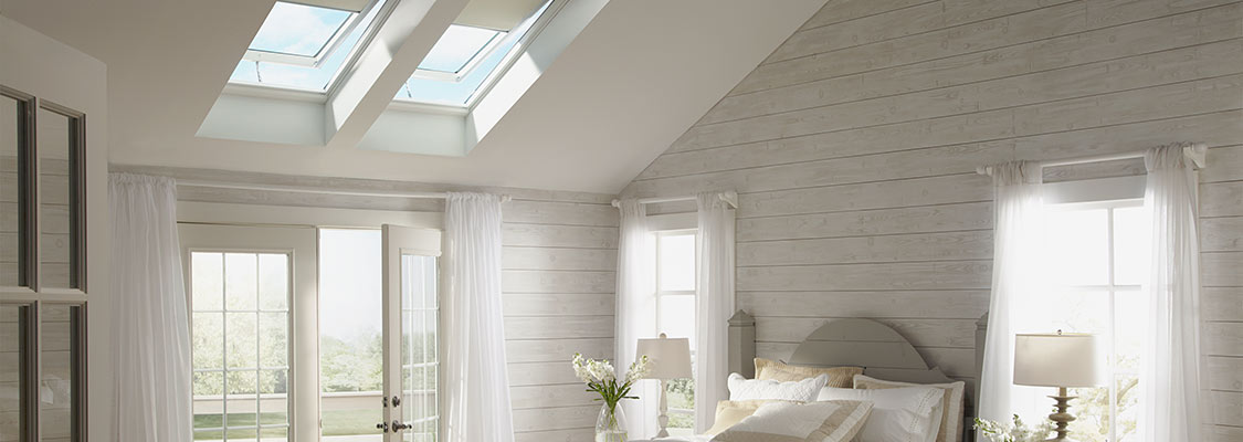 "Two Velux Solar Powered ""Fresh Air"" skylights with light filtering blinds installed on the roof provide ample daylight to this bedroom"