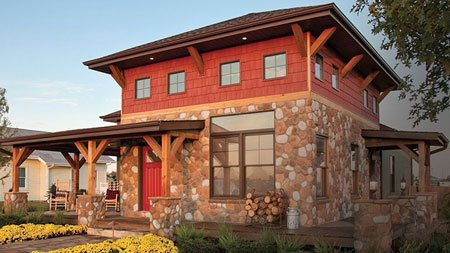 The curb appeal of this stone and wood shingle Craftsman style home is enhanced by the Ply Gem windows and red front entry door