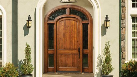The unique arched-top and transom surround of this Rogue Valley custom wood front entry door complements the curved entryway of this upscale home