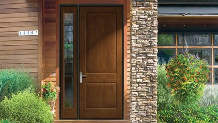 Grand entryway of this Southwest inspired home features Therma Tru oversized front entry door with sidelite from their Classic-Craft Rustic Collection